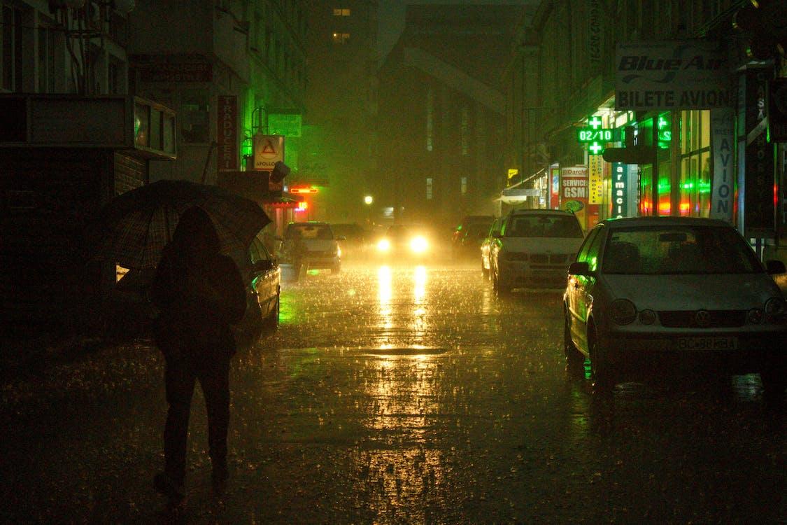 Person Holding Umbrella Walking on Sidewalk during Night Time