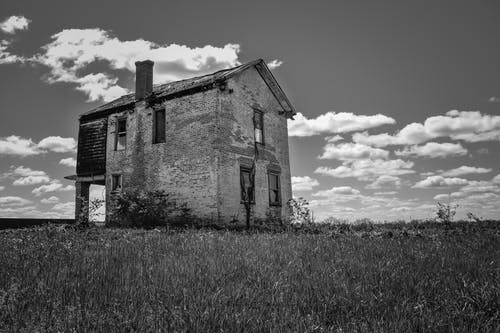 Low angle black and white of old masonry building with weathered walls and chimney on grass lawn under sky with clouds