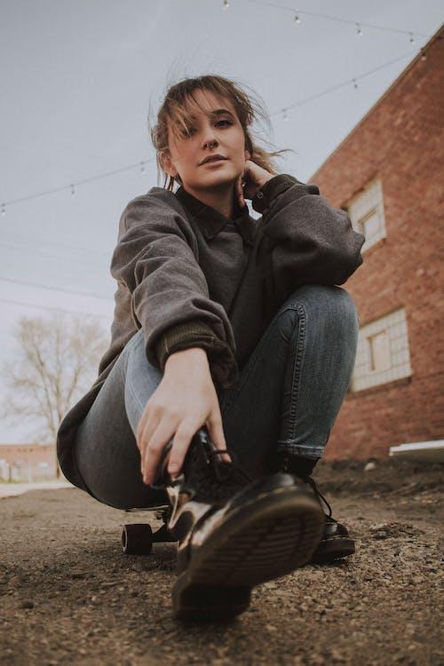 Photo of Woman Sitting on Her Black Longboard