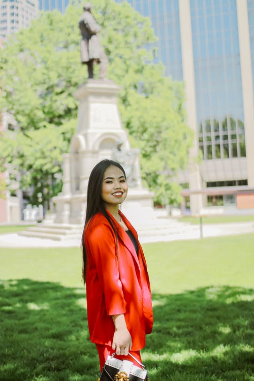 Photo of Woman in Red Blazer Standing on Grass Field
