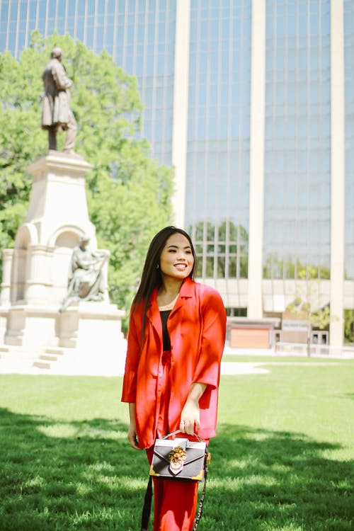 Woman in Red Blazer While Standing on Green Grass Field