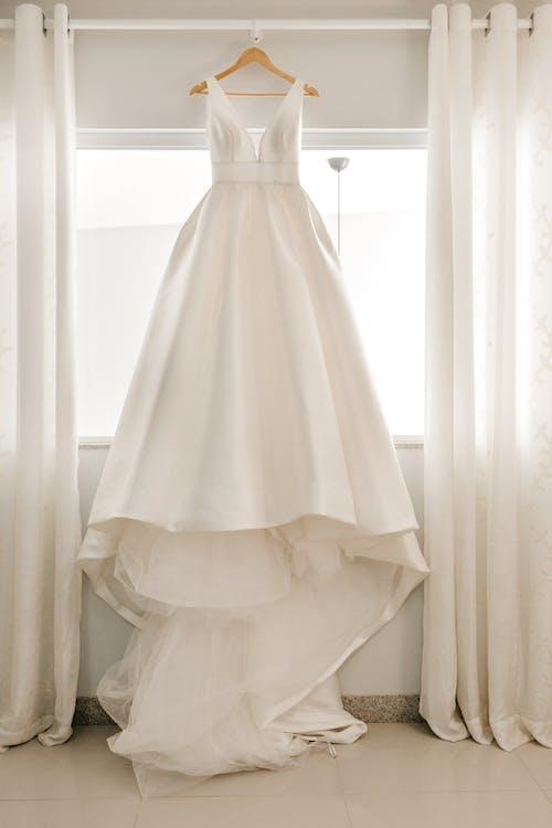 White wedding dress on hanger near window