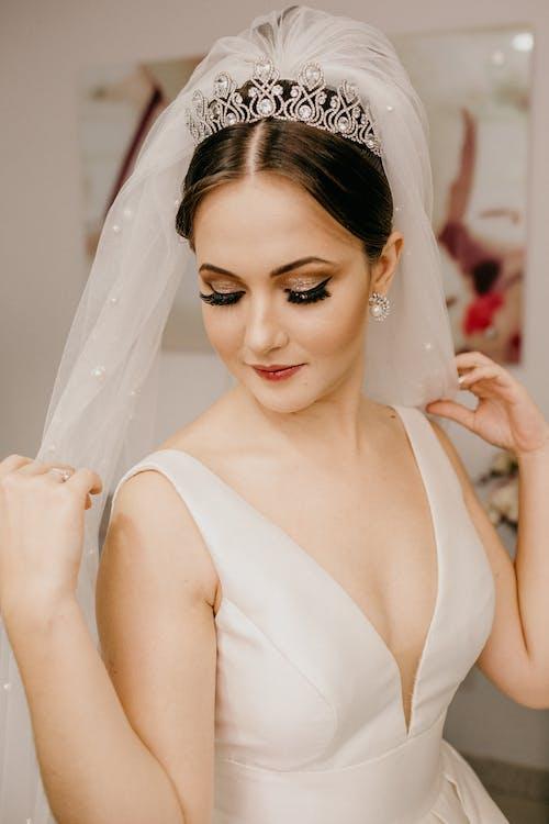 Charming bride in wedding dress with makeup in bijouterie