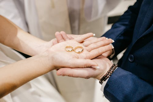 Crop couple with wedding rings during festive event