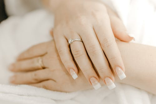 From above of hands of crop anonymous woman with classic manicure and ring with precious stone on wedding day