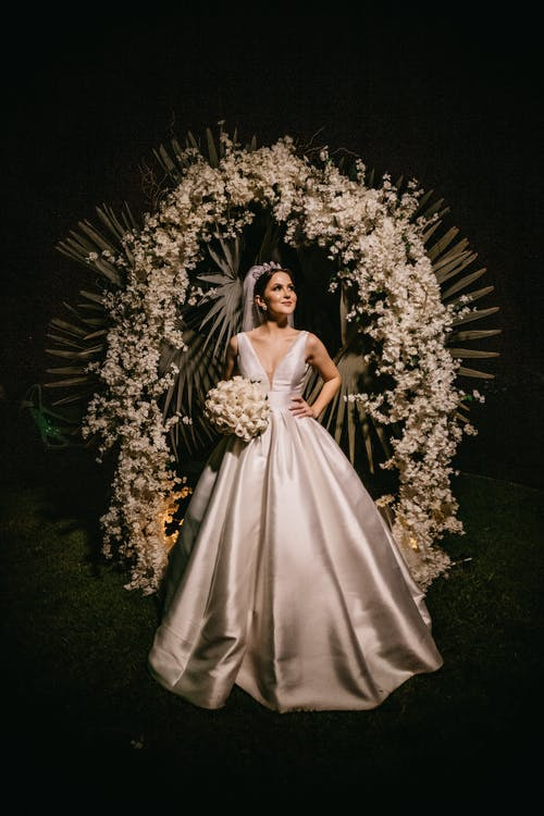 Happy bride near flower decoration on black background