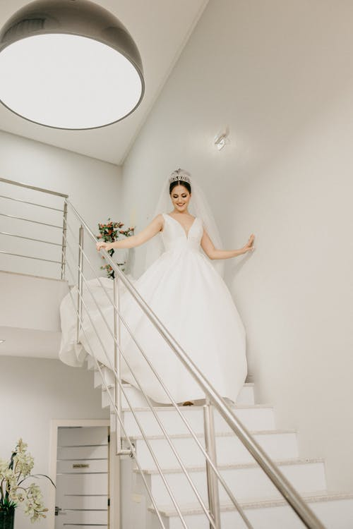 Happy bride in white dress walking down stairs