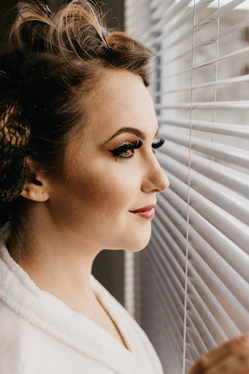Side view of content female with bright makeup in white bathrobe looking at window pensively
