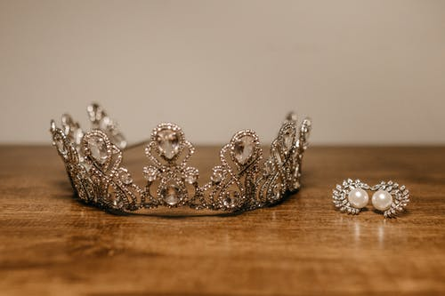 Crown and earrings placed on wooden table