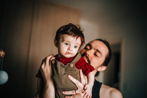 Man holding little boy in arms