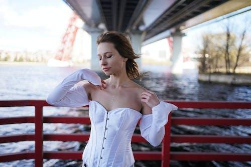 Sensual stylish woman with eyes closed near boat railing