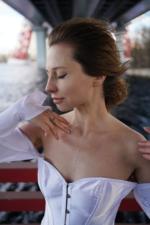 Elegant charming female with sequins on face and low neck standing with eyes closed near boat railing and raising hands gracefully during river cruise