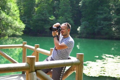 Man in Gray and Black Stripe Shirt Taking Photo of Green Lake