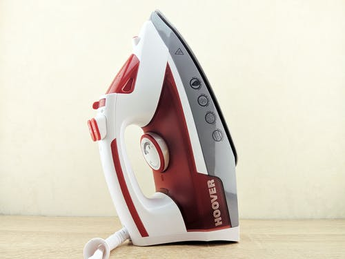 Contemporary multi functional wired iron of white and red colors placed on heel rest on white surface