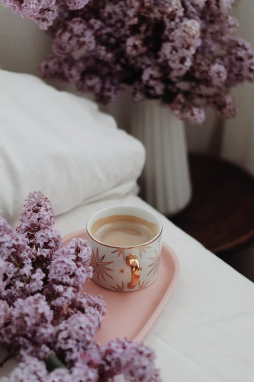 Cup of coffee on tray on bed decorated with lilac