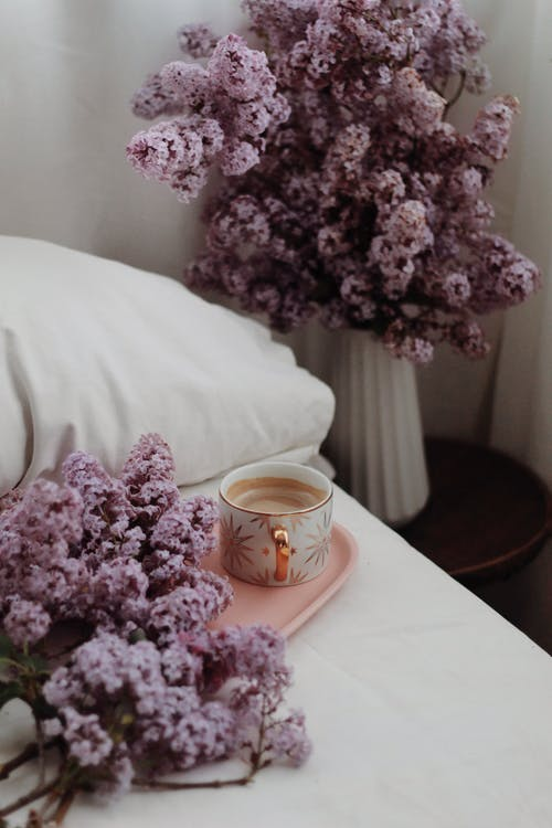 Bouquets of lilacs in bedroom near cup of coffee