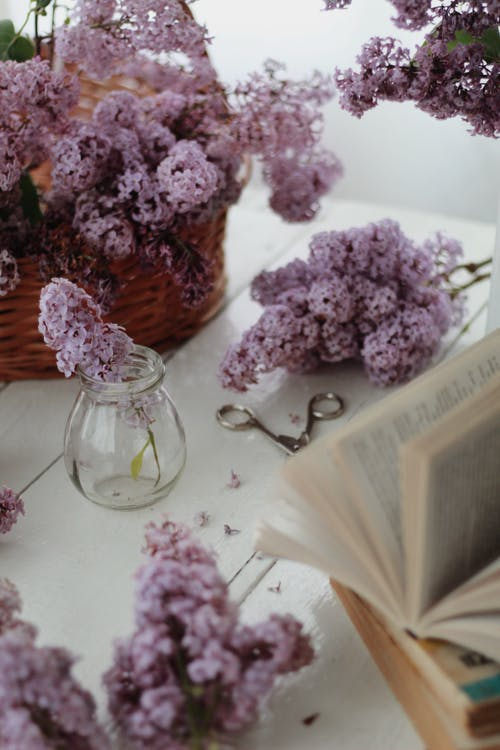 High angle arrangement of wicker basket with blooming lilac flowers placed on table near stacked books and jar vase