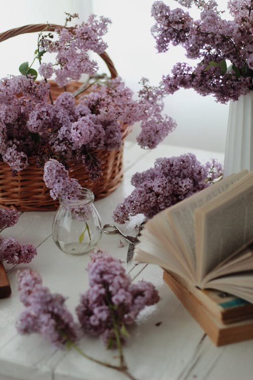 Bouquet of lilacs in basket on table near books