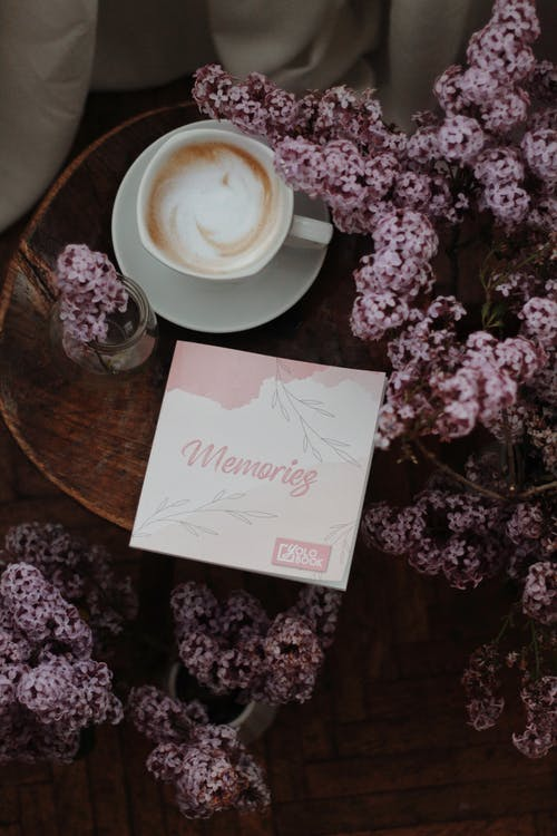 From above composition of delicious fresh cappuccino served on round bedside table with postcard decorated with delicate lilac bouquet on spring morning