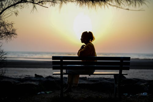 Woman Sitting on Bench during Sunset