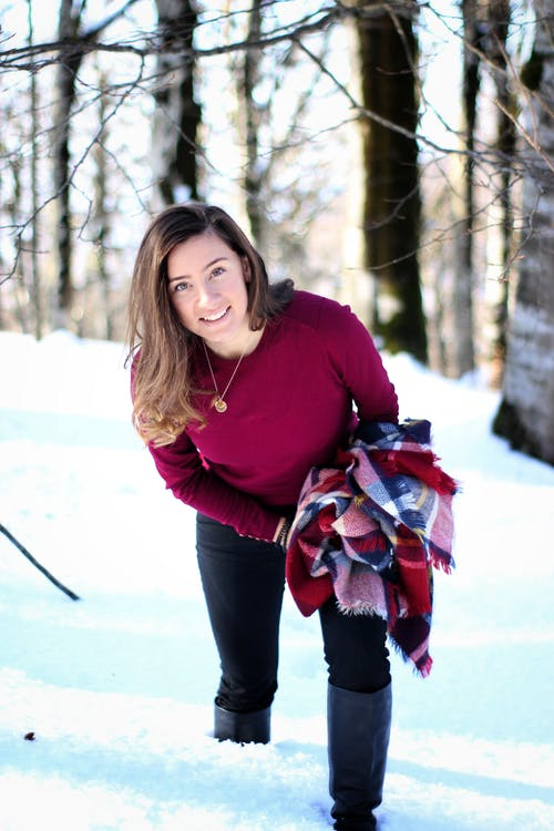 Woman in Red Sweater and Black Pants Standing on Snow Covered Ground