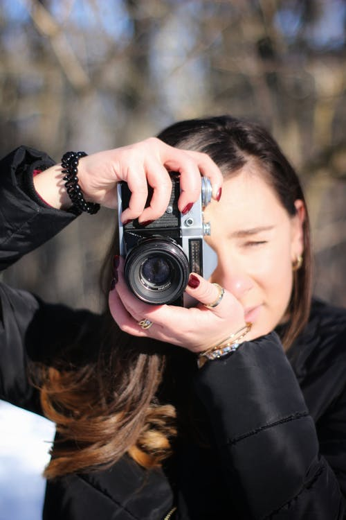 Woman in Black Jacket Holding Gray and Black Camera