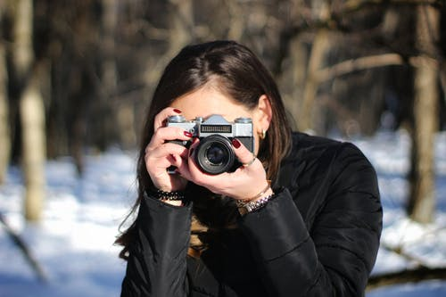 Woman in Black Jacket Holding Black and Silver Camera