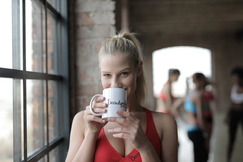 Cheerful young woman drinking tea in gym