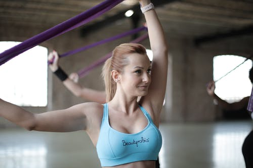 Young sportswoman doing stretch exercise with elastic band in modern gym