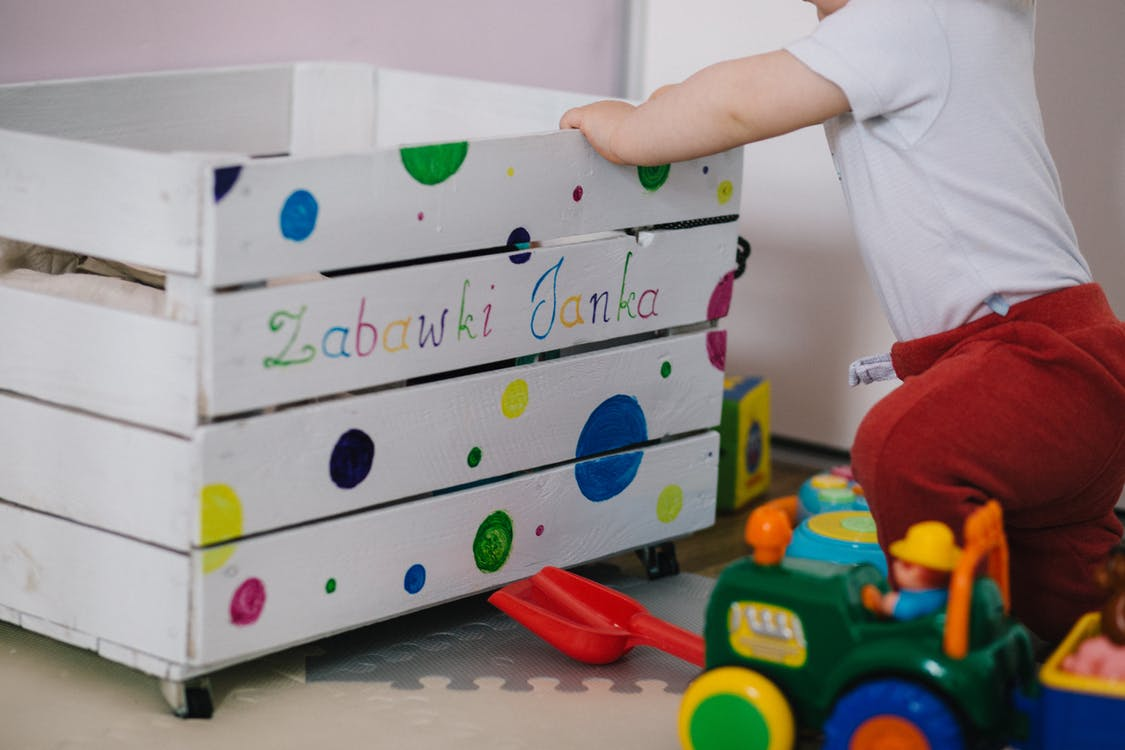 Toddler in Front of Wooden Storage