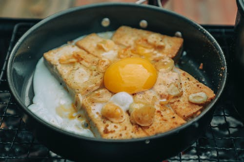 High angle tasty homemade egg toasts on pan roasting on barbecue grid in backyard