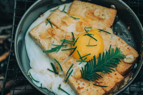 From above appetizing grilled toasts under egg with rosemary cooked on frying pan on barbecue grid