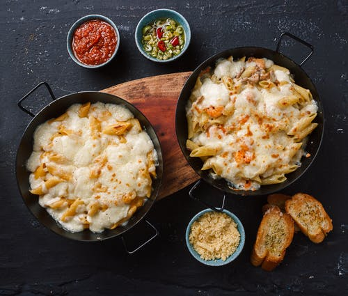 Top view of freshly prepared Italian penne pasta with cheesy sauce served in pans and placed on wooden cutting board near traditional sauces and bruschettas
