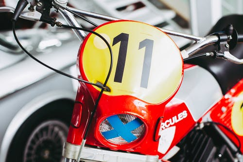Red and White Motorcycle With Yellow and White Round Sticker