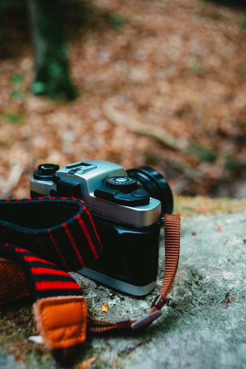 Black and Red Dslr Camera on Ground