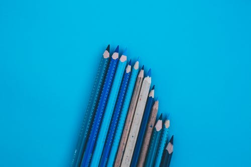 Blue and White Pencils on Green Surface