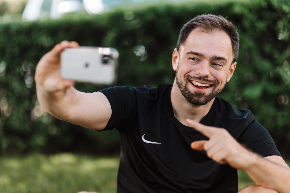 Smiling Man in Black Shirt Taking a Selfie