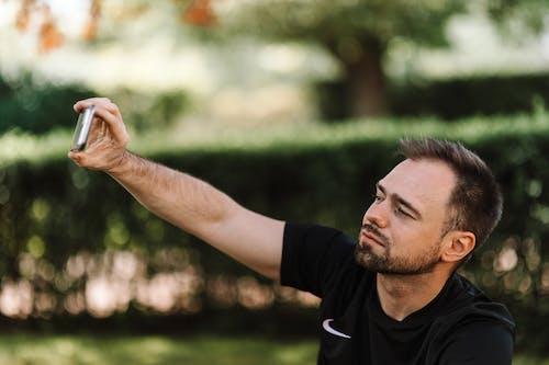 Man in Black Shirt Taking Selfie