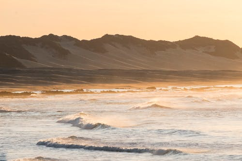 Waving sea surrounded by sandy dunes and mountains during sundown