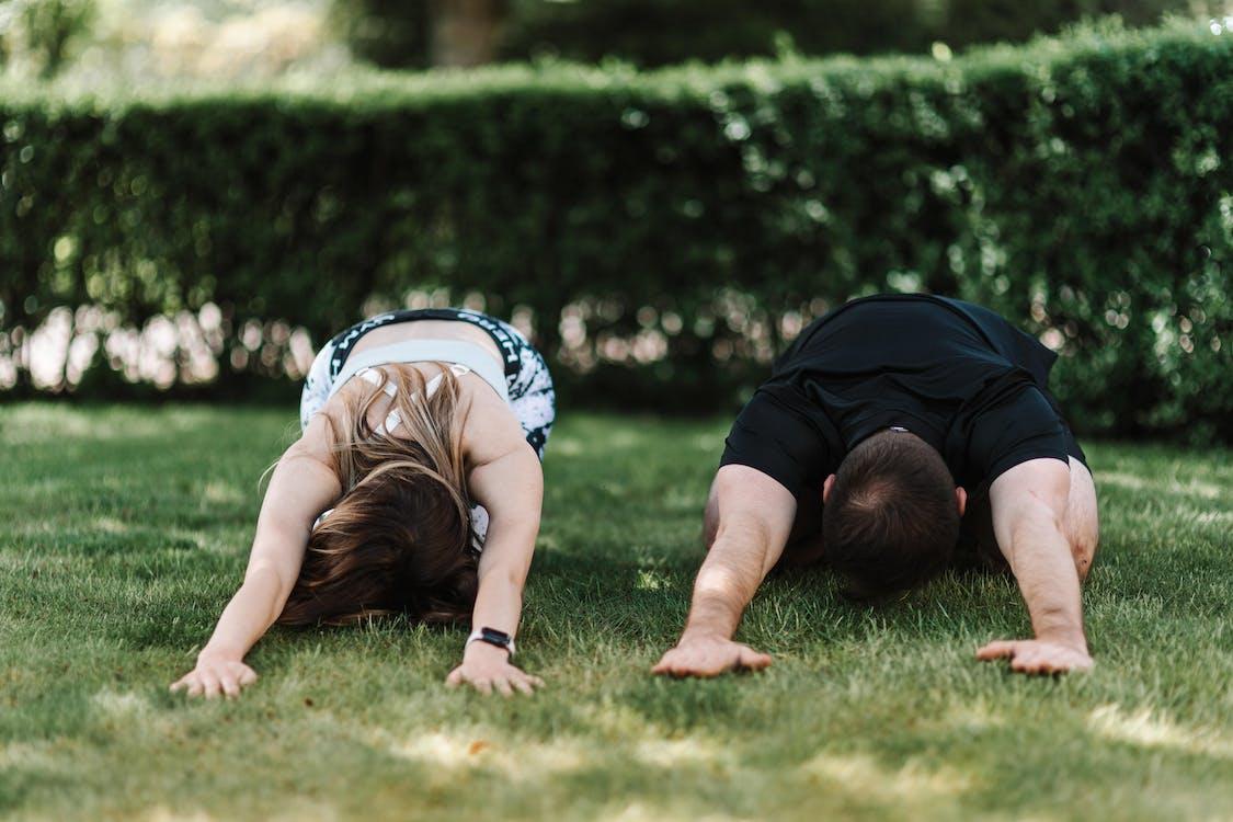 Woman in Black T-shirt Lying on Green Grass Field