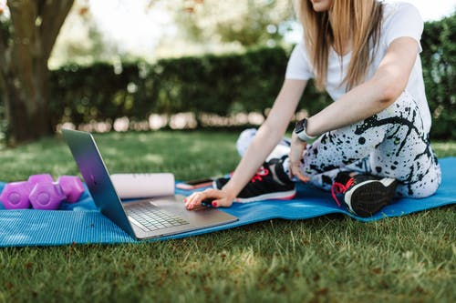 Shallow Focus Photo of a Woman in Activewear Using a Laptop while Sitting on a Yoga Mat