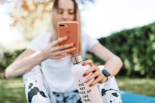 Shallow Focus Photo of a Woman Taking Picture of Her Water Bottle