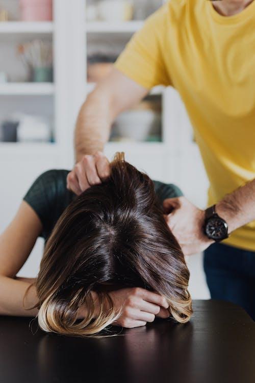 Person Grabbing Woman's Shoulders