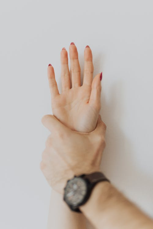 Man Hand Oppressing a Hand of a Woman on the Wall