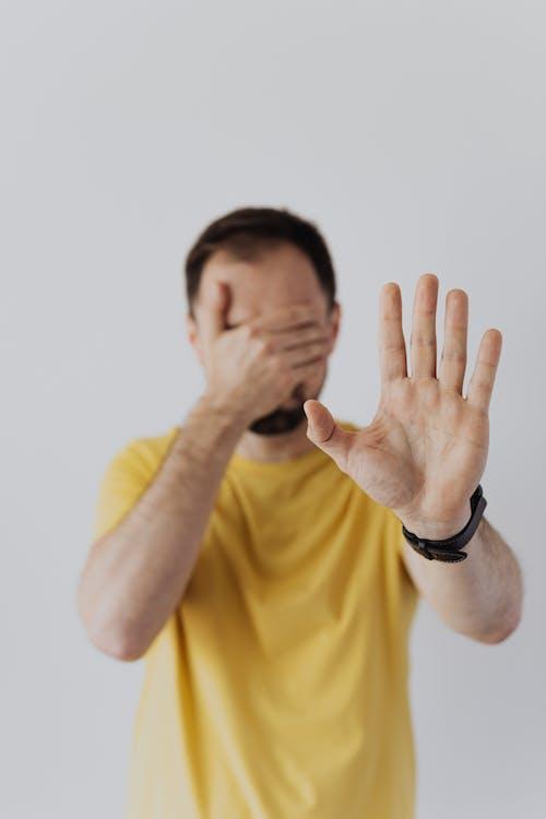 Kostenloses Stock Foto zu abdeckung, erschrocken, gelbes shirt