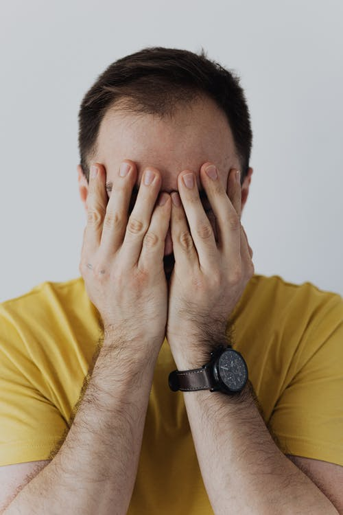 Man in Yellow Shirt Covering His Face with His Hands