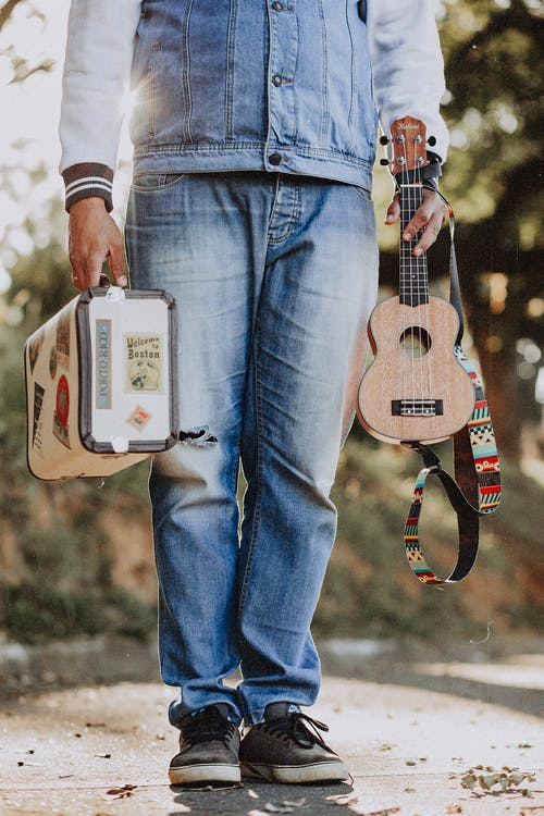 Person in Blue Denim Jeans Carrying Brown Acoustic Guitar