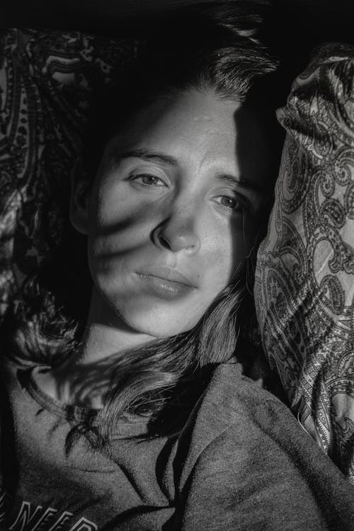 Black and white of thoughtful young female lying on pillow and looking away