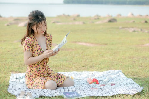 Romantic young Asian female student in light dress sitting on blanket on grassy ground near sea and reading interesting book