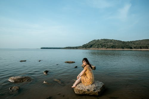 Dreamy young ethnic woman resting on sea shore against blue sky